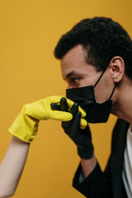 Photo of man kissing hand with face mask on