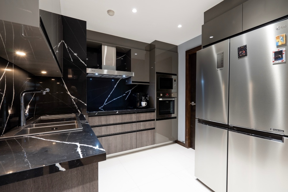 Modern elegance is carried through the kitchen with stainless steel appliances, married with black marble for the countertops and backsplashes.