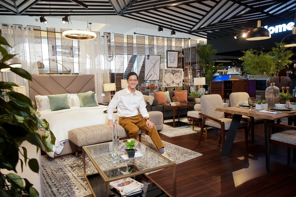 Interior Designer Nix Alañon sits in a vignette of his home decor and furniture picks at All Home, Evia.