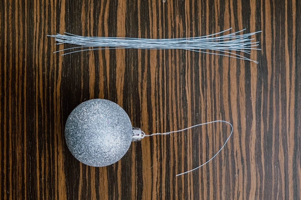 Anton Barretto suggests replacing the strings or ribbons that usually come with Christmas ornaments.  Instead, use 4-inch wires for the ornaments' snug fit on the Christmas tree branches.