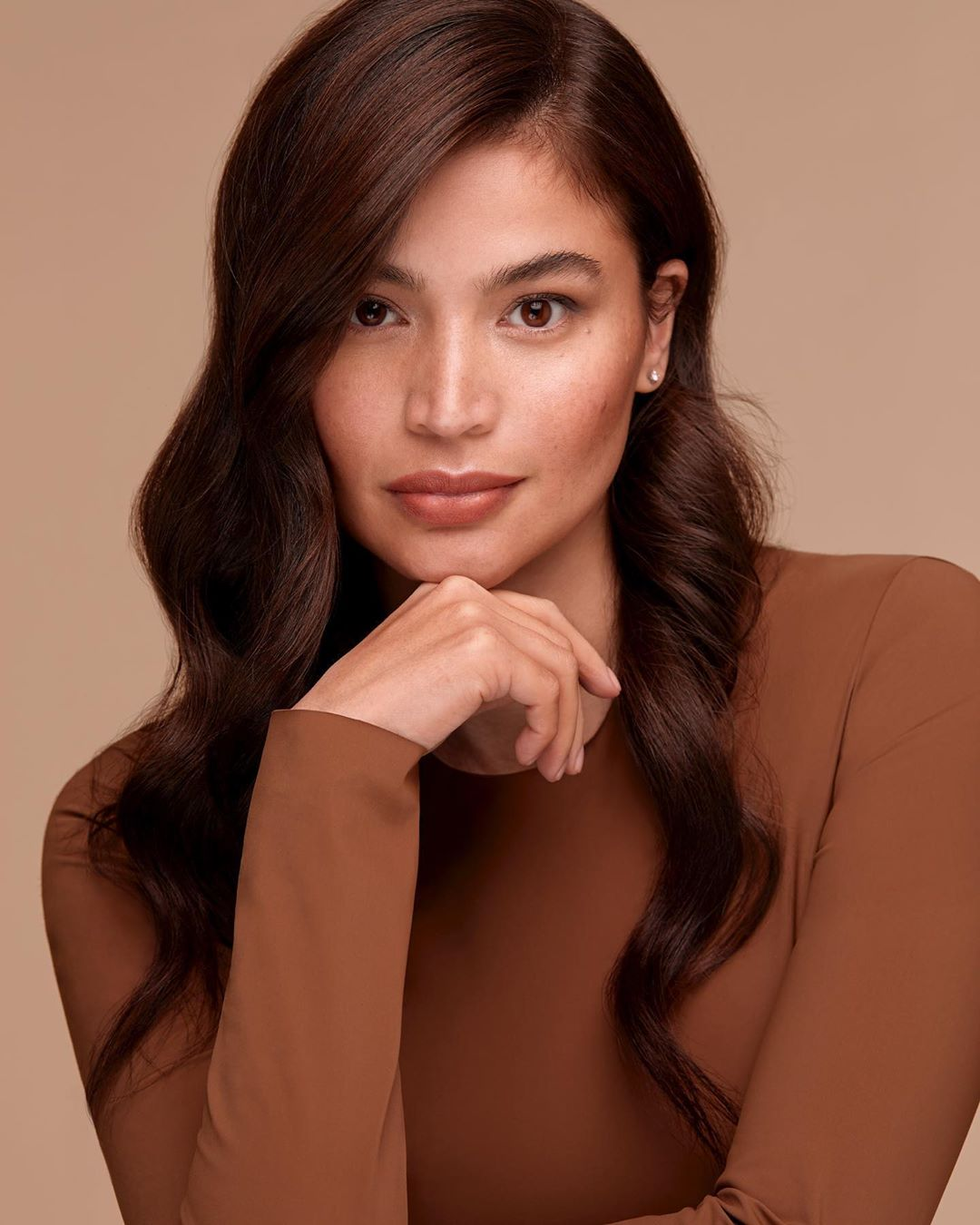 Anne is wearing the Illuminating Skin Tint SPF 30 in Butterscotch, Loose Powder in Light, Brow Mascara in Taupe, Priming + Mattifying Stick, Multitasking Color Stick in Mimosa (eyes and cheeks), and Cocoa (as contour), Lip Switch in Espresso