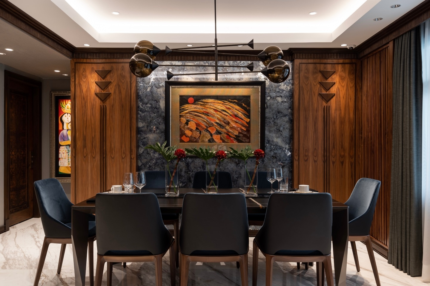 In the dining room, walnut veneers and solid walnut panels to hide the air conditioning units are used.  Hints of polished metal finishes, as in the chandelier above the dining table polish the look.